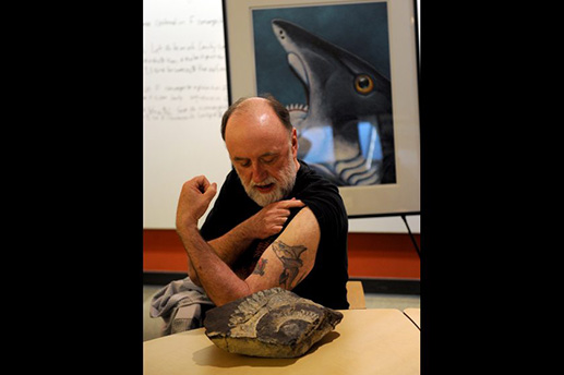 Ketchikan artist Ray Troll shows his ratfish tattoo next to the Helicprion fossil at the UAA ConocoPhillips Integrated Science building in Anchorage, AK on Wednesday, May 13, 2015. Barrow, AK geologist Richard Glenn found the buzz-tooth shark fossil Helicoprion on the North Slope when he was a student. The provenance of the fossil was lost when the Smithsonian miscategorized it. Troll was instrumental in having it found in the collection and getting Glenn credit for finding the only Helicprion fossil found in Alaska. The fossil will be on display at the Alaska SeaLife Center in Seward, AK this summer. Bob Hallinen / ADN