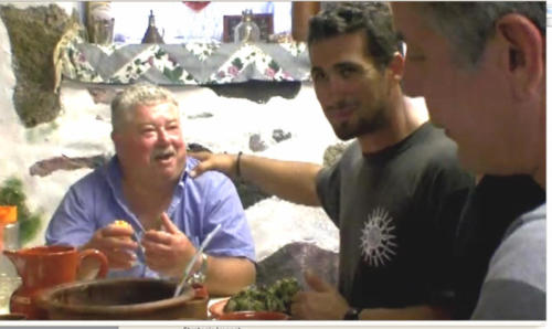 Anthony Bourdain on the right and a guy wearing a 'Fabric of Life' shirt next to him, somewhere in Greece