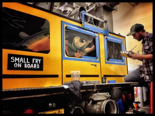 Hollis Swan helps to paint the back of the bus